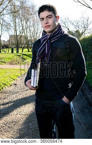 Handsome Young Teenage Male Student Walking To School In Sunshine, Carrying Books And Rucksack