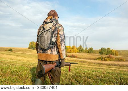 Hunter On The Background Walking On The Field. Hunter With A Backpack And A Hunting Gun In Autumn Se