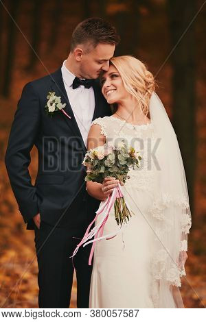 Happy Young Married Couple In Golden Yellow Fall Autumn Park. Beautiful Bride And Stylish Groom Hugg
