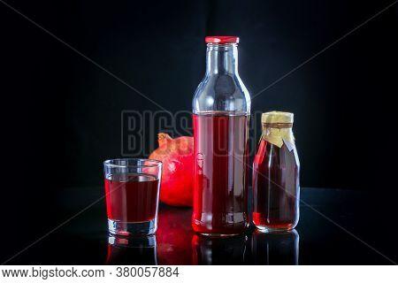 Pomegranate Juice With Fresh Pomegranate Fruit On Black Background.