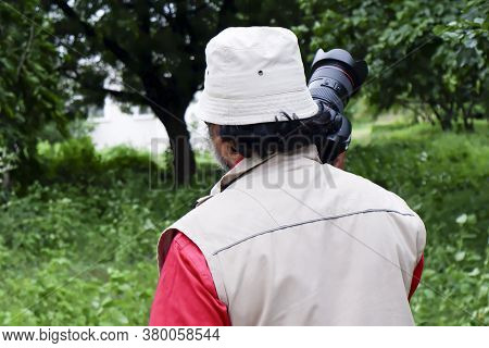 A Closeup Backside View Of Young Professional Photographer Holding Camera Picture