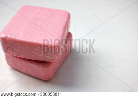 Two Bars Of Pink Handmade Soap Tied With Twine On The White Wooden Background. Selective Focus, Copy