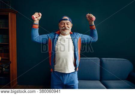 Elderly sportsman doing exercise with dumbbells