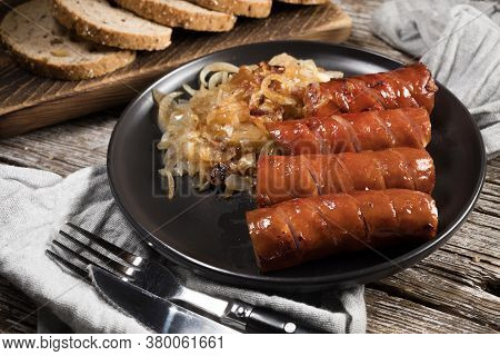 Fried Sausage With Onion On Black Plate.