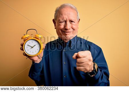 Senior grey haired man holding vintage alarm clock over yellow background annoyed and frustrated shouting with anger, crazy and yelling with raised hand, anger concept