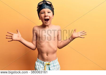 Cute blond kid wearing swimwear and swimmer glasses celebrating victory with happy smile and winner expression with raised hands