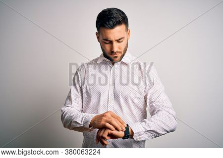 Young handsome man wearing elegant shirt standing over isolated white background Checking the time on wrist watch, relaxed and confident