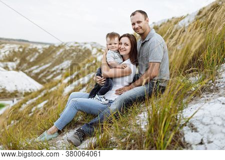 Happy Young Family Near Lake, Pond. Family Enjoying Life Together At Meadow. People Having Fun In Na