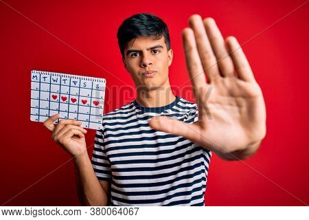 Young handsome man holding calendar with hearts over isolated red background with open hand doing stop sign with serious and confident expression, defense gesture