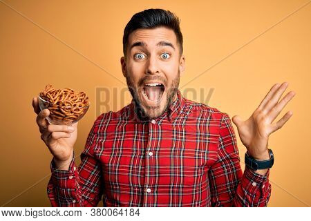 Young handsome man holding bowl with baked German pretzels over yellow background very happy and excited, winner expression celebrating victory screaming with big smile and raised hands