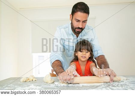 Handsome Dad Teaching Daughter To Bake. Focused Girl And Her Father Kneading And Rolling Dough On Ki