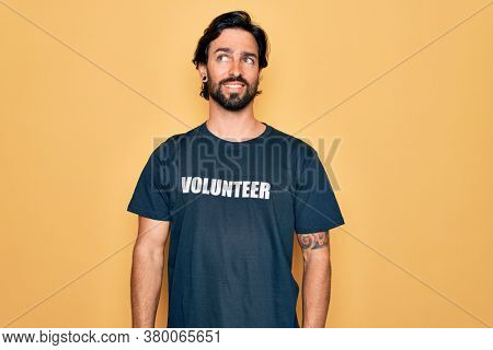 Young handsome hispanic volunteer man wearing volunteering t-shirt as social care smiling looking to the side and staring away thinking.