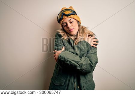 Young brunette skier woman wearing snow clothes and ski goggles over white background Hugging oneself happy and positive, smiling confident. Self love and self care