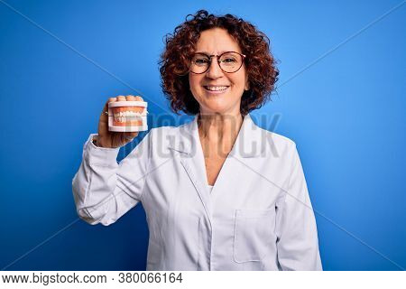 Middle age dentist woman wearing coat holding plastic denture teeth over blue background with a happy face standing and smiling with a confident smile showing teeth