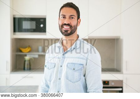 Cheerful Attractive Dark Haired Latin Man Posing In Kitchen, Looking At Camera And Smiling. Medium S