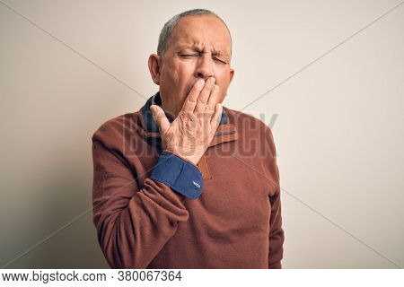 Senior handsome man  wearing elegant sweater standing over isolated white background bored yawning tired covering mouth with hand. Restless and sleepiness.