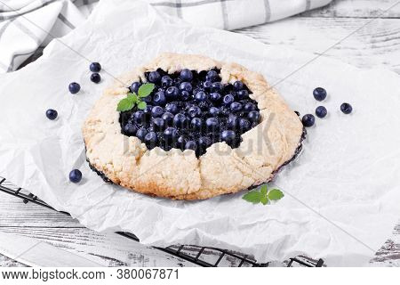 Shortbread Galette With Bilberry On The Baking Parchment On The White Wooden Table