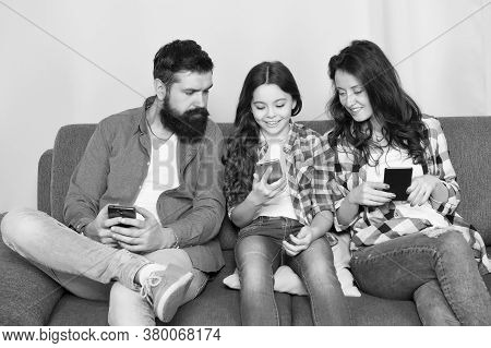 Play Game Application. Online Family. Mom Dad And Daughter Relaxing On Couch. Family Spend Weekend O