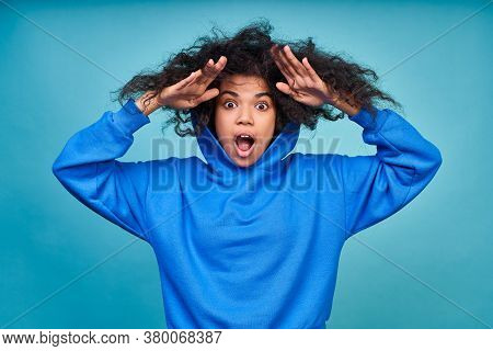 A Surprised, Shocked, Discouraged Young African American Woman, Wearing A Blue Hoodie, Holds Her Bla