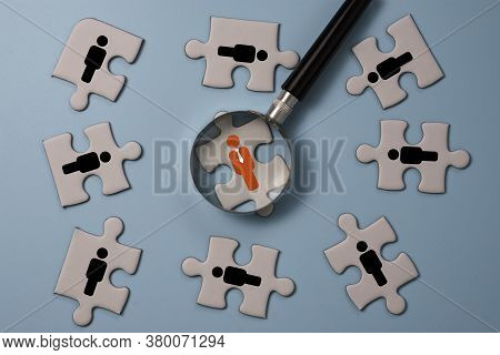 Hand Holding Magnifier Glass To Searching Red Human Icon On Jigsaw Puzzle Among Black People Icon. H
