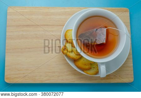 Hot Earl Grey In A Cup Served With Crispy Bread On A Wooden Plate