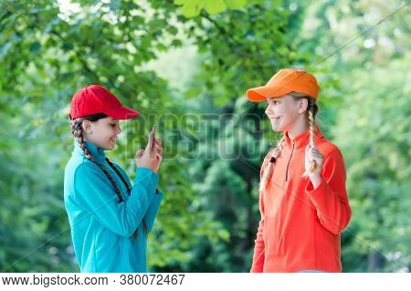 Best School Friends Make Photo On Mobile Phone. Concept Of Friendship. Happy Girls Wear Sport Clothe