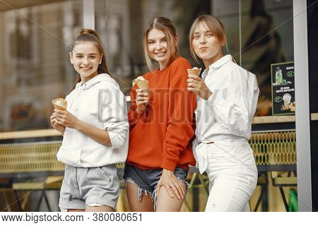 Girls Standing In A Summer City With Ice Cream