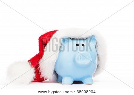 blue piggy bank wearing santas hat