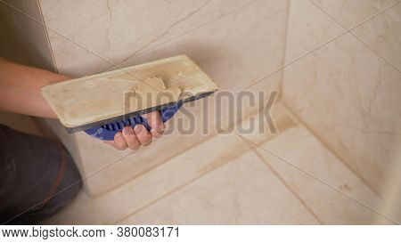 The Hand Of Man Holding A Rubber Float And Filling Joints With Grout. The Worker Is Rubbing The Tile