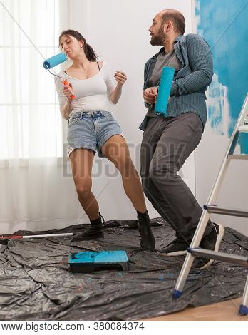 Joyful Couple Redecorating, Dacing And Singing With Roller Brush Dipped In Blue Paint. Apartment Red