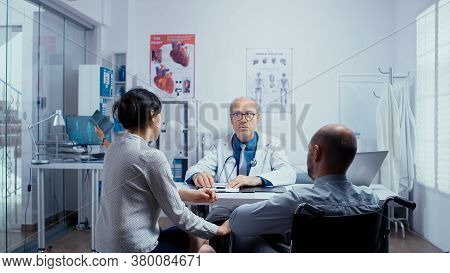 In Modern Clinic For Disabled And Handicapped Recovery, Young Man In Wheelchair Is Seeking Consultat
