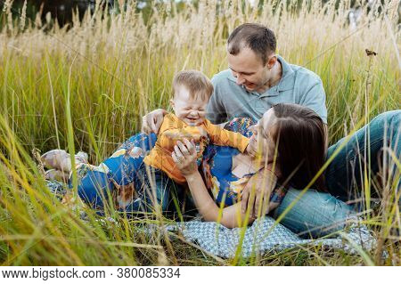 Happy Family Having Fun Outdoors In Grass. Family Enjoying Life Together At Meadow. Mother, Father,
