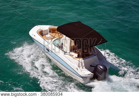 Angled Overhead View Of An Upscale Sport Runabout Motorboat Powered By A Singe Outboard Engine.