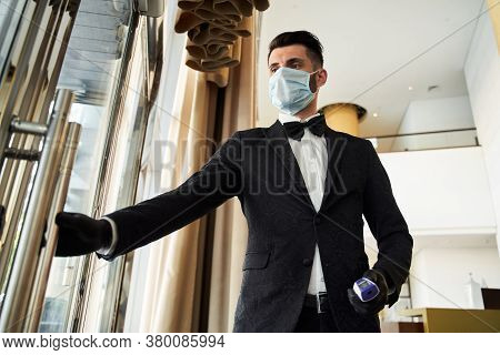 Young Hotel Receptionist Working In Medical Mask And Rubber Gloves