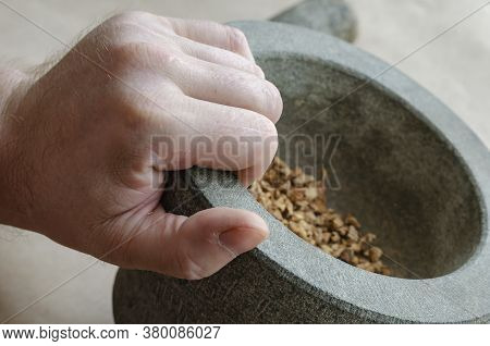 Hand Holds Stone Mortar With Crushed Medicinal Herbs And Roots. Caucasian Middle-aged Man. Alternati