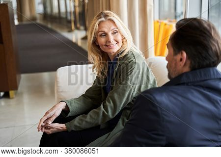 Mirthful Woman Smiling To Her Husband While Sitting Indoors