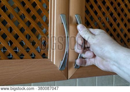 Male Hand Opens A Kitchen Cabinet. Wooden Kitchen Cabinet Door. Life Style. Selective Focus.