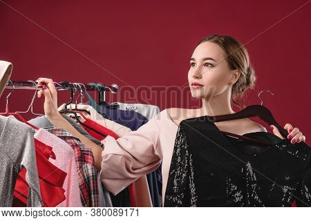 Beautiful Women Chooses And Tries On Clothes On A Red Background. The Concept Of Choosing And Buying