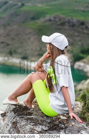 A Beautiful Woman Traveler In A White Cap And T-shirt, Sits On A Stone High In The Mountains Above T