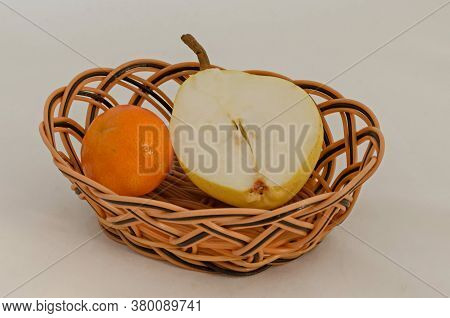 Fresh Ripe Orange And A Piece Of Yellow Pear In A Basket, Ready To Eat, Sofia, Bulgaria