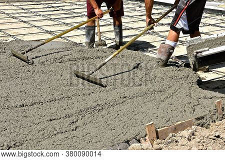 Several Concrete Workers Push The Wet Mud Over The Reinforcing Rods Of A New Driveway Site.
