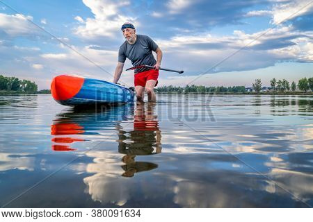 senior male stand up paddler is launching his paddleboard  on a lake for morning workout in northern Colorado, solo paddling as a form of social distancing
