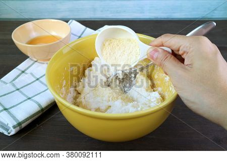 Hand Adding Parmesan Cheese Onto Dough In Mixing Bowl For Baking Brazilian Cheese Bread