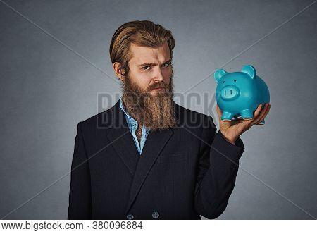 Finance, Money. Serious Man Holds Piggy Bank. Bearded Man Holds Piggy Bank Full Of Money Over Gray B