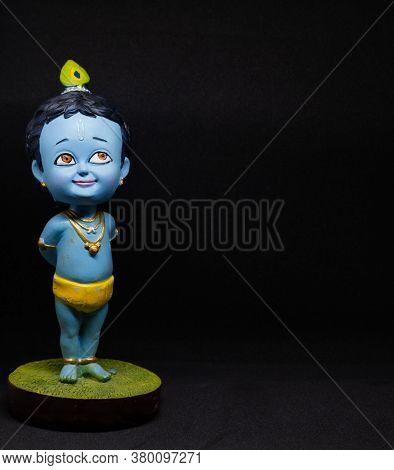 Cute And Innocent Idol Of Hindu God Lord Krishna As A Child With Black Background And Left Oriented.