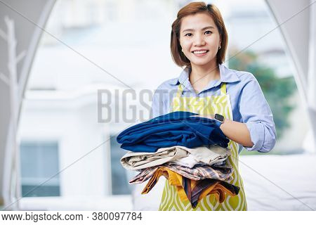 Portrait Of Smiling Young Vietnamese Housewife Holding Stack Of Washed And Dry Clothes
