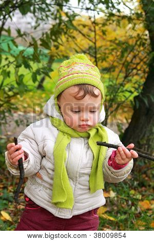 Fun Baby Girl Looking On Branches On Autumn Nature
