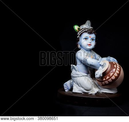 Cute And Innocent Idol Of Hindu God Lord Krishna As A Child Eating Butter. Celebrated During Janmash