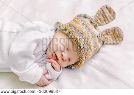 Cute Newborn Baby In A Funny Hat With Bunny Ears Is Sleeping Sweetly In A Crib On A White Soft Sheet