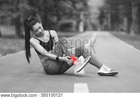 Sad Asian Girl Having Ankle Pain After Jogging In Park, Massaging Red Sore Spot, Sitting On Path, Bw